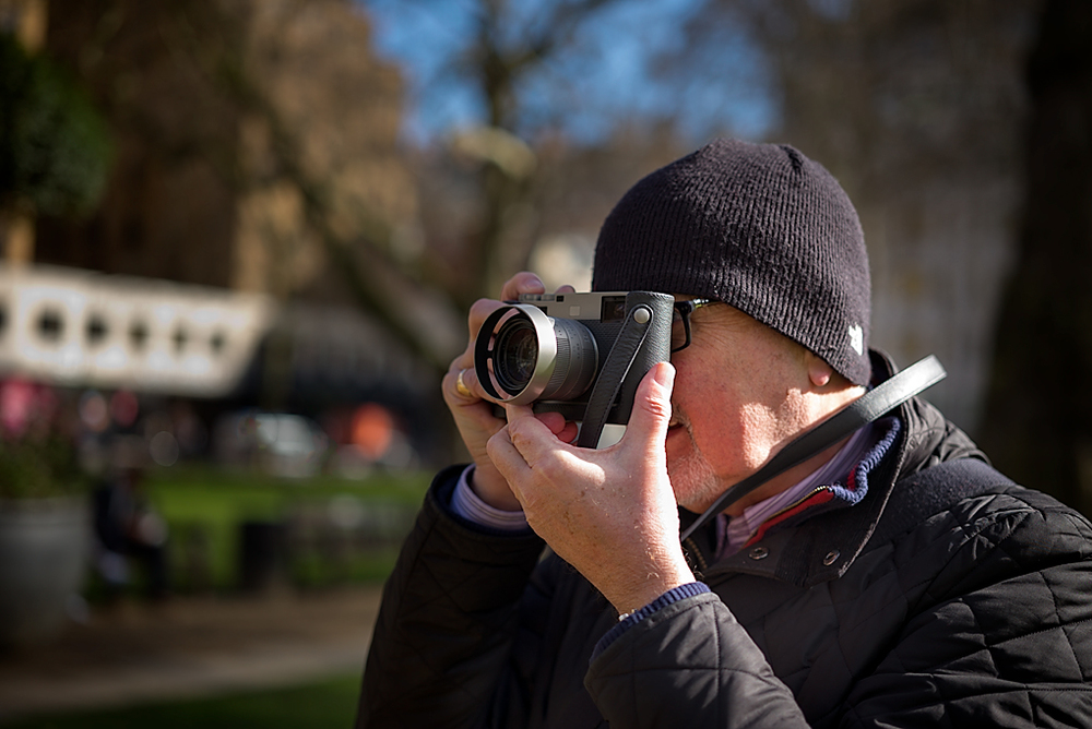 The M60 singsin Berkeley Square: Thisbeautiful camera comes with a fine leather case and neck strap as you can see here. Since there are no strap lugs on the body, use of the Leica-designed case is mandatory (Pictureof  Editor Evans in action on a chilly day, taken byGeorge James, Leica M-P with 50mm Apo-Summicron-M ASPH)