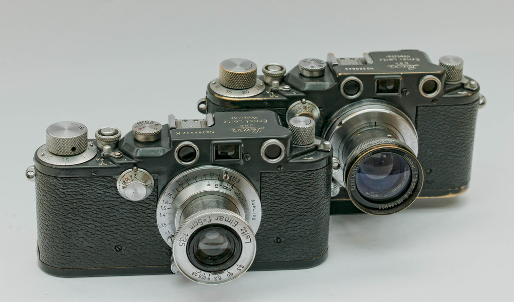 Two grey IIIcs from 1942. One is a IIIc and the other on the front left is a IIIcK, the K standing for 'Kugellager' (ball bearing in English). These grey models are sometimes treated as military cameras but neither of these cameras appears in Dr Luigi Cane's book of military serial numbers produced for the German Leica Historical Society (Leica Historica e.V.), which I treat as my bible on this subject. Some cameras from this period were produced in grey paint not for any military requirement but because chrome materials were in short supply because of the war.