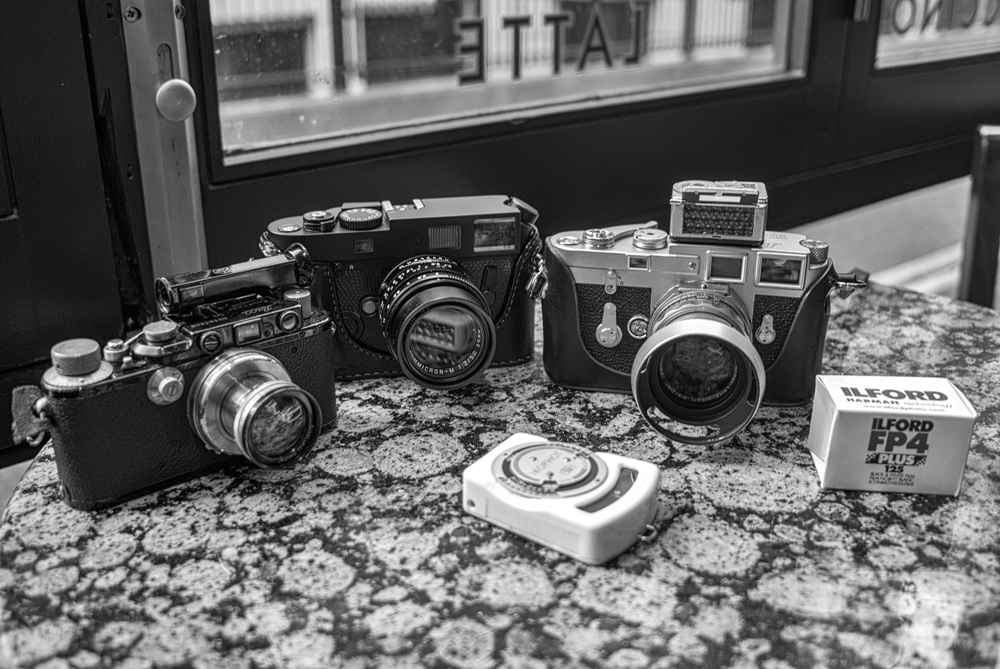 On the starting grid: Three film cameras, one roll of film and two rather mad camera nerds. Left to right: Leica III and 5cm Summar, plus Winkelsucher (1936); Neil the M7 (2004) and 50mm Apo-Summicron; Leica M3 double-stroke (1957) with 50mm Summicron dual-range (with Sekonic light meter on top), Ilford FP4 and Adam