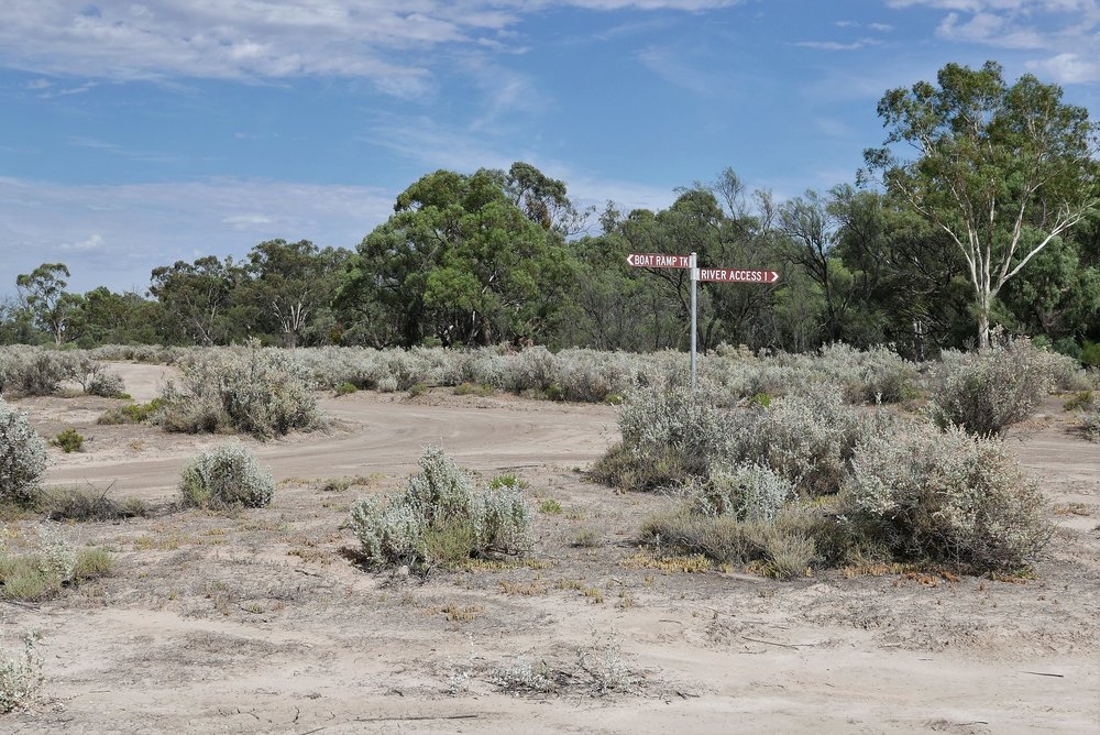 On shore, only saltbush and Eucalypts, and a single sign post breaks the monotony