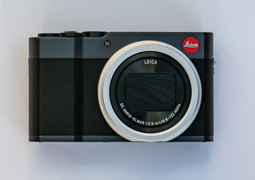 A handsome rangefinder-style camera with excellent proportions. Note the depth of the top plate which effectively complements the faux-leather body. On some cameras, particularly those from Fuji, the top plate is too narrow and rather ruins the harmonious appearance. The hand grip is very practical — and essential at 360mm — and the extra large lens housing dominates the appearance. I think it would have looked better in body colour or black.