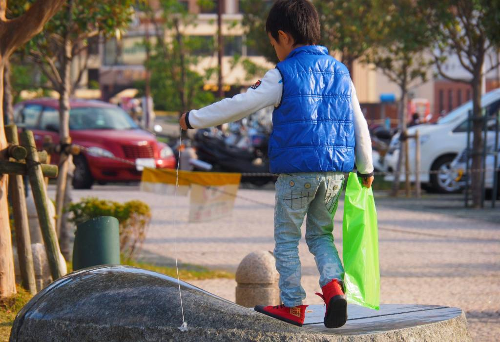Amazingly sad, for me; a boy with his teeny, faithful (Space Shuttle?) toy. Not a dog, not a cat, but a bit of plastic pet on a string. For me, besides the bright colours, it's a picture of an imaginary friend, a world of his own. Nagasaki, Japan.