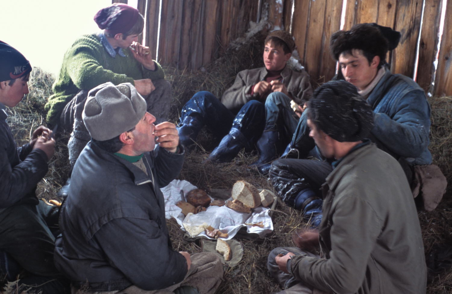 Men eating in a bark in midwinter above the village of Jidegsegpataka Transylvania Romania after loading their sledges (Leica M6 and 35mm f/1.4 Summilux)