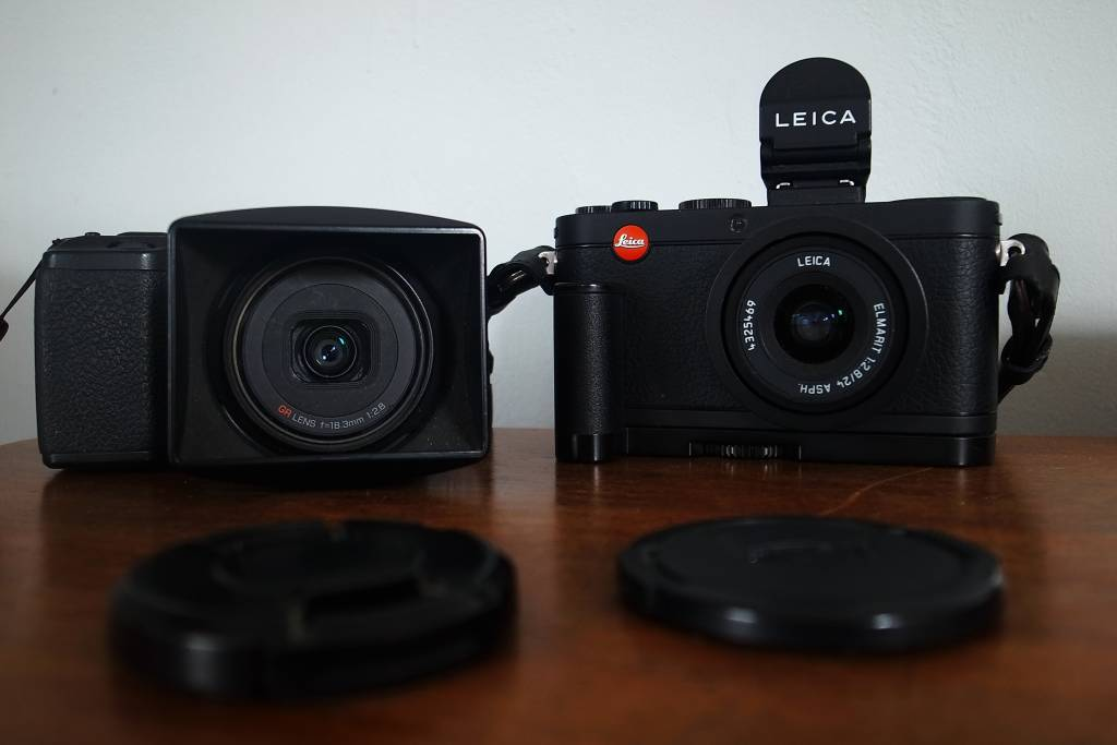 Side-by-side comparison. In this picture the Ricoh GR features the ugly lens hood proboscis while the Leica is equipped with the Leica Hand Grip and the VF-2 electronic viewfinder (Image Jean Perenet)