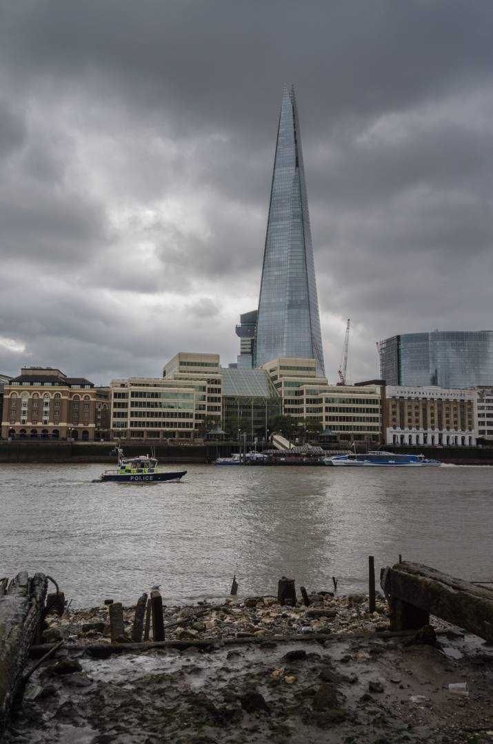 Police launch passing the old barge beds and modern Shard