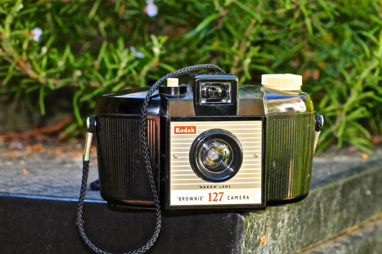 """This is the second version, with vertical ribbing on the body, and a larger viewfinder and larger lens (marked 'Dakon'). The curved rear side of the camera was not just a design affectation; it had a proper purpose: the very simple cheap curved plastic lens on the front wasn't corrected to give a """"flat field"""" result on flat film, so the centre of the image was fairly sharp, but the edges would have been blurred and unfocused if <i>the film itself</i> hadn't also been curved, following the guides inside the curved back of the camera! I didn't know that at the time, but was just so taken with the bowl-like shape of this simple, elegant form-follows-function black-body-white-buttons plastic Brownie"""