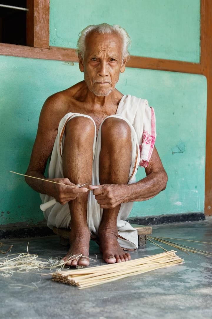 Kaka, an elderly resident, strips cane probably for making masks at Uttar Kamalabari Satra