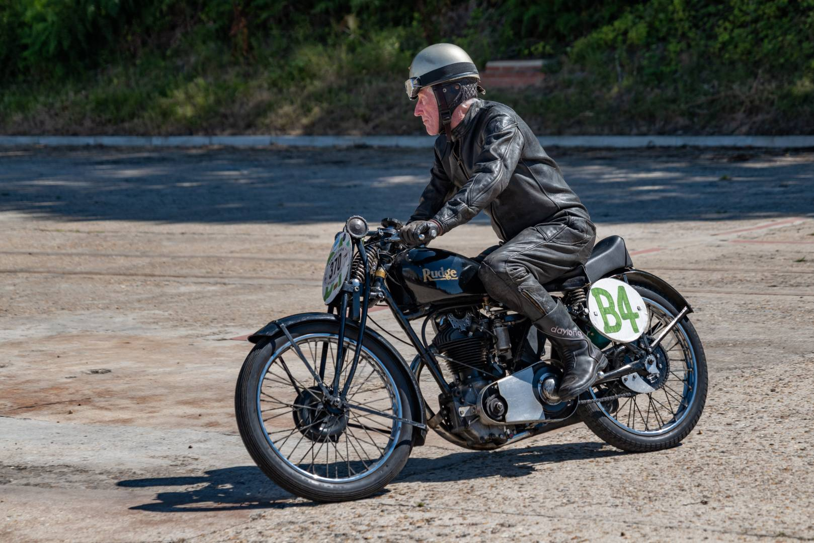 Motorcycle racing as it used to be, a pre-war Rudge, although the rider is dressed more for the late fifties with his one-piece leathers
