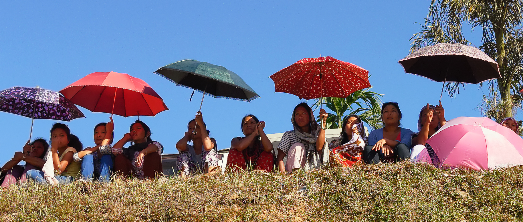Women, shielding themselves from the hot sun, watch the match in Mon from a spot overlooking the field